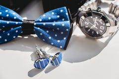 Zapatos de cuero negros, reloj, corbata de lazo azul y mancuernas, en un travesaño blanco de la ventana Accesorio para el vestido Fotos de archivo libres de regalías