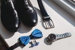 Zapatos de cuero y correa negra, reloj, corbata de lazo azul y mancuernas, en un travesaño blanco de la ventana Accesorio para el Fotografía de archivo