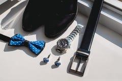 Zapatos de cuero y correa negra, reloj, corbata de lazo azul y mancuernas, en un travesaño blanco de la ventana Accesorio para el Foto de archivo