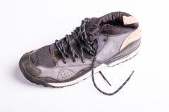 Zapatos de entrenamiento usados viejos con los lazos en un fondo blanco Fotografía de archivo