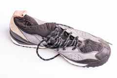 Zapatos de entrenamiento usados viejos con los lazos en un fondo blanco Foto de archivo
