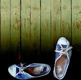 Zapatos de gimnasia gastados de los pantalones vaqueros contra una pared de madera del tablón Imagen de archivo libre de regalías