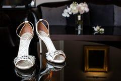 Zapatos de la boda con las joyas en una tabla del espejo fotografía de archivo