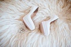Zapatos de la boda de la novia con los tacones altos y el pendiente brillante de plata Fotos de archivo libres de regalías