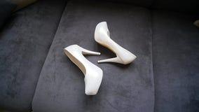 Zapatos de la boda del ` s de la novia en el sofá almacen de video