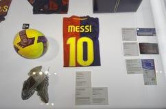 Zapatos de la bola y del fútbol de la camisa de Leo Messi en el museo del estadio del campo de Nou Barcelona, España Foto de archivo libre de regalías