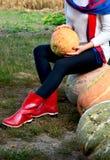 Zapatos de la lluvia de la calabaza de otoño y de madera rojos con el fondo de los leavs imagen de archivo libre de regalías