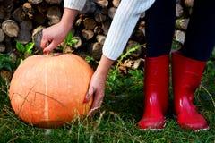 Zapatos de la lluvia de la calabaza de otoño y de madera rojos con el fondo de los leavs imagenes de archivo