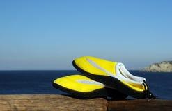 Zapatos de la playa contra fondo del mar Fotos de archivo libres de regalías