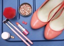 Zapatos de las mujeres y accesorios del maquillaje en color en colores pastel en un fondo azul Imagen de archivo libre de regalías