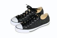 Zapatos de lona negros con el fondo blanco Foto de archivo libre de regalías
