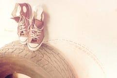 Zapatos de lona viejos en el neumático usado Fotografía de archivo libre de regalías