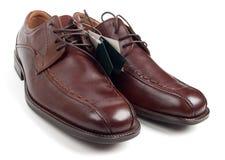 Zapatos de los nuevos hombres con las escrituras de la etiqueta imagen de archivo
