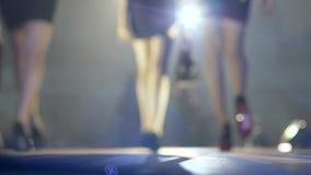 Zapatos de moda en las piernas del modelo delgado que caminan en el podio en la iluminación del proyector almacen de video