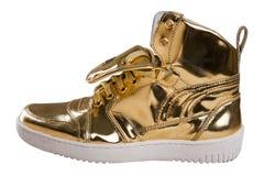 Zapatos de oro del deporte en blanco Foto de archivo libre de regalías