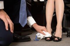Zapatos de pulido de los businesswomans del hombre Fotografía de archivo libre de regalías