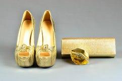 Zapatos de tacón alto del oro, bolso de embrague y perfume en un backgr gris Imagenes de archivo