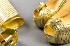 Zapatos de tacón alto del oro, bolso de embrague y perfume en un backgr gris Fotos de archivo