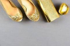 Zapatos de tacón alto del oro, bolso de embrague y perfume en un backgro gris Imagen de archivo libre de regalías