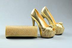Zapatos de tacón alto del oro y bolso de embrague en un fondo gris Imágenes de archivo libres de regalías