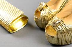 Zapatos de tacón alto del oro y bolso de embrague en un fondo gris Fotografía de archivo