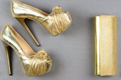 Zapatos de tacón alto del oro y un bolso de embrague en un fondo gris Fotos de archivo libres de regalías