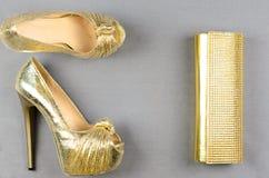 Zapatos de tacón alto del oro y un bolso de embrague en un fondo gris Foto de archivo