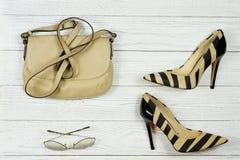 Zapatos de tacón alto del ` s de las mujeres, bolso y gafas de sol elegantes del ` s de las mujeres en un fondo blanco imagenes de archivo