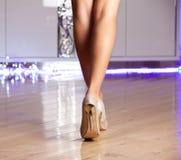 Zapatos de tacón alto elegantes del oro de la mujer que llevan Foto de archivo