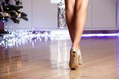 Zapatos de tacón alto elegantes del oro de la mujer que llevan Imagen de archivo libre de regalías