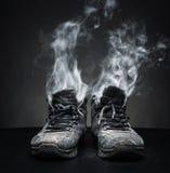 Zapatos de trabajo viejos en humo Fotos de archivo libres de regalías