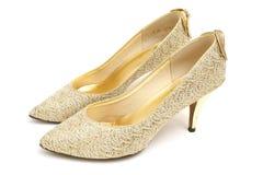 Zapatos del alto talón del oro Foto de archivo