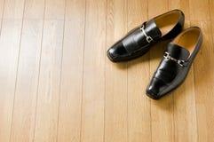 Zapatos del asunto en suelo de madera Imagen de archivo libre de regalías