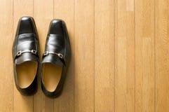 Zapatos del asunto en suelo de madera Fotos de archivo libres de regalías