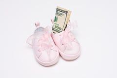 Zapatos del bebé con la cuenta $100 adentro Foto de archivo