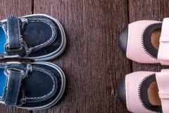 Zapatos del bebé y de la muchacha en fondo de madera Calzado del niño Visión superior Foto de archivo libre de regalías