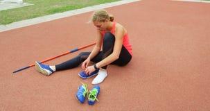 Zapatos del deporte del atleta que llevan de sexo femenino en el lugar de deporte 4k almacen de video