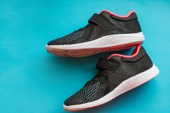 Zapatos del deporte en fondo azul Zapatos negros rosados del deporte de los niños aislados Pares de los nuevos deportes, zapatill foto de archivo libre de regalías
