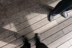Zapatos del empleado dos que se coloca en tablón Imágenes de archivo libres de regalías