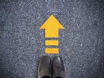 Zapatos del negro de la zapatilla de deporte de Selfie en el camino concreto con li amarillo de la flecha Fotografía de archivo