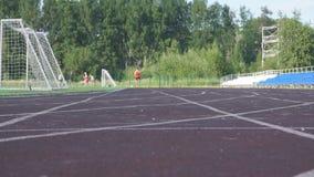 Zapatos del oro del atleta que llevan que corren a través del cielo azul brillante en la cámara lenta metrajes