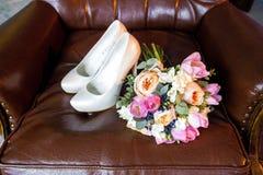 Zapatos del ramo y de la novia de la boda en un fondo marrón Fotos de archivo