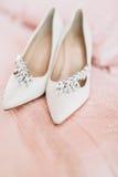 Zapatos del ` s de la novia para el día de boda en la hoja de cama Fotos de archivo