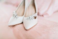 Zapatos del ` s de la novia para el día de boda en la hoja de cama Fotografía de archivo libre de regalías