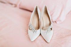 Zapatos del ` s de la novia para el día de boda en la hoja de cama Foto de archivo