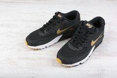 Zapatos del ` s de las mujeres de Nike Air Max - zapatillas de deporte en negro, en el fondo de madera blanco Nike es un global Fotografía de archivo