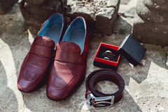 Zapatos del ` s de los hombres de la cereza, correa y anillos de bodas en una caja prepare los accesorios del ` s en el día de bo Imagen de archivo