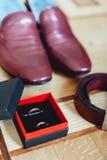 Zapatos del ` s de los hombres de la cereza, correa y anillos de bodas en una caja prepare los accesorios del ` s en el día de bo Foto de archivo libre de regalías
