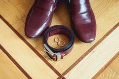 Zapatos del ` s de los hombres de la cereza, correa y anillos de bodas en una caja prepare los accesorios del ` s en el día de bo Imagen de archivo libre de regalías