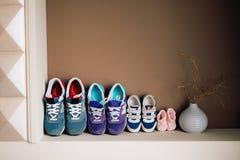 Zapatos del ` s de los niños al lado de un adulto Fotos de archivo libres de regalías